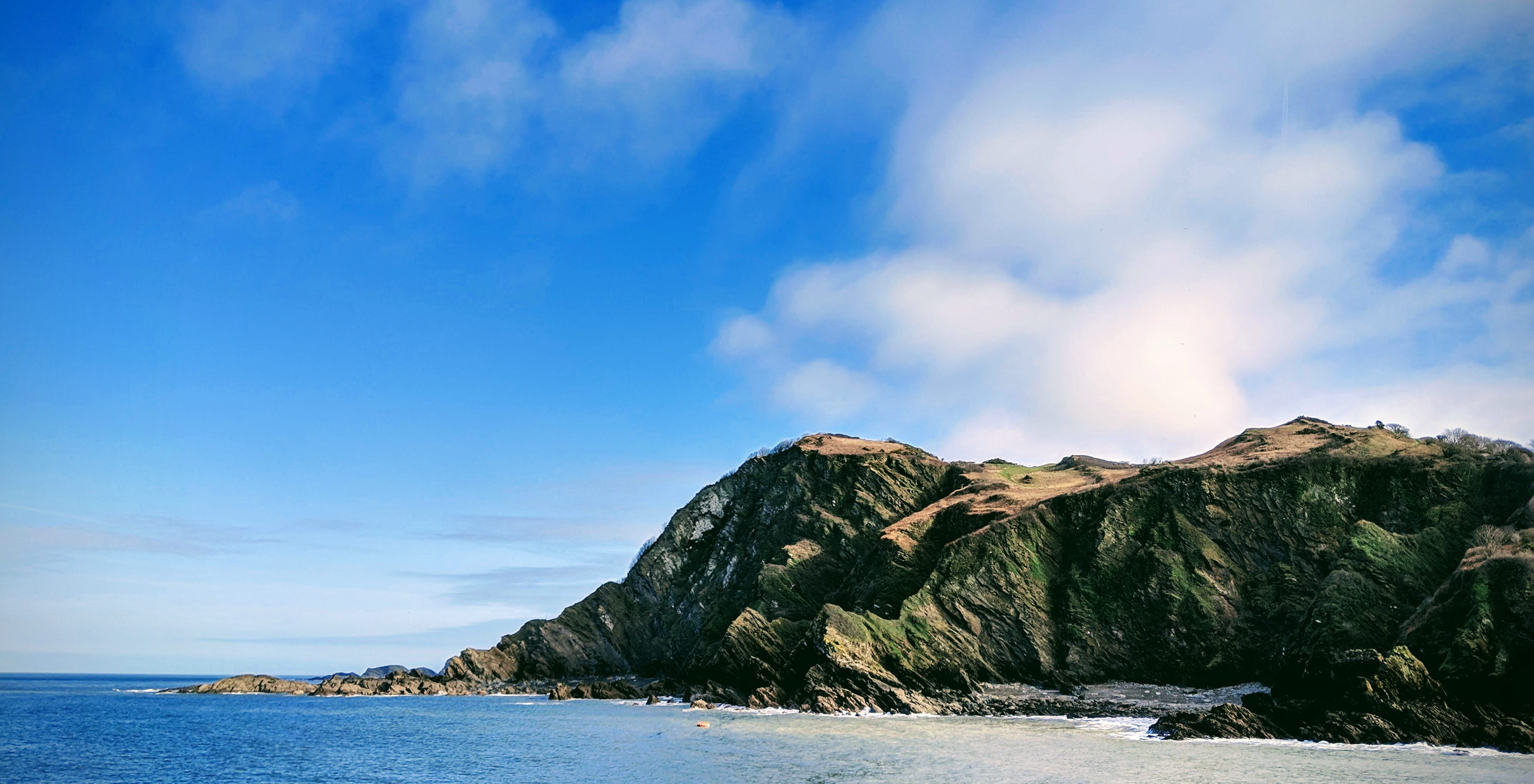 blue sky and sea with hills in background Ilfracombe harbour